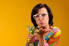 Pretty girl in glasses and snowdrops. In the hands over yellow background Royalty Free Stock Images