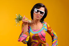 Pretty girl in glasses and snowdrops. In the hands over yellow background Stock Images