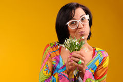Pretty girl in glasses and snowdrops. In the hands over yellow background Stock Image
