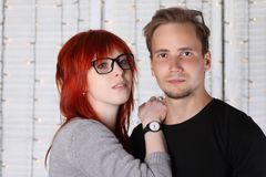 Pretty girl in glasses and young guy pose together. Near wall in white studio with garlands of lanterns Stock Images