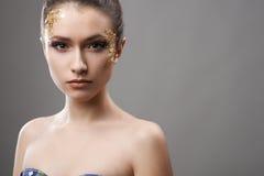 Pretty girl with golden make-up art Stock Photos