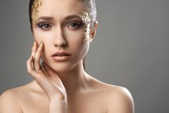 Pretty girl with golden make-up art Stock Images