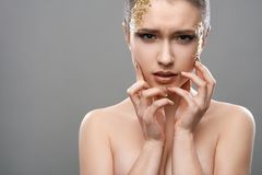 Pretty girl with golden make-up art Stock Photography