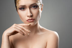 Pretty girl with golden make-up art Stock Photos
