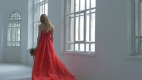 Pretty girl in gorgeous red dress walking past the stock video