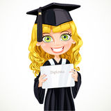 Pretty girl in gown graduate holding a diploma Royalty Free Stock Images