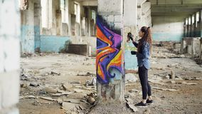 Pretty girl graffiti artist is decorating old damaged column inside empty industrial building with abstract pictures. Pretty young girl graffiti artist is stock video footage
