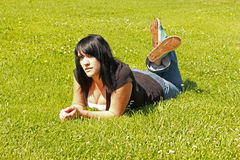 Pretty Girl On The Grass On Her Stomach. Pretty girl relaxing at the city park Royalty Free Stock Image