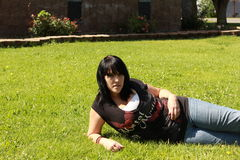 Pretty Girl On The Grass On Her Side. Pretty girl relaxing at the city park Royalty Free Stock Images