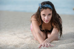 Pretty girl with great body sitting on the sand Stock Photography