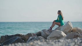 Pretty girl in green blazer, denim shorts and sneakers is sitting on stone seashore enjoying amazing sea view and. Sometimes smiling to camera 4k stock video footage