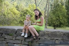 Pretty girl in green dress sitting with little brother on stone wall near Ainsa, Aragon, in the Pyrenees Mountains, Province of Hu Stock Images