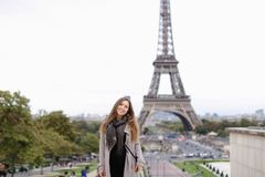 Pretty woman in grey coat standing with Eiffel Tower background in Paris. Pretty girl in grey coat standing with Eiffel Tower background in Paris. Concept of royalty free stock image