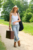 Pretty girl with guitar and baggage on the road Stock Photo