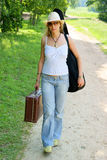 Pretty girl with guitar and baggage walking Royalty Free Stock Photography