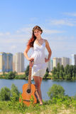 Pretty girl with a guitar outdoors Royalty Free Stock Photos