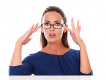 Pretty girl with hand on glasses looking at you Stock Photography