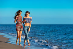 Pretty girl has a fun with her girlfriend on the beach.  Stock Images