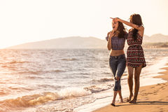 Pretty girl has a fun with her girlfriend on the beach Stock Photography