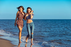 Pretty girl has a fun with her girlfriend on the beach Stock Images