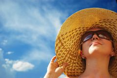 Pretty girl in hat. Portrait of young beautiful woman in straw hat and sunglasses on blue sky background Royalty Free Stock Photography