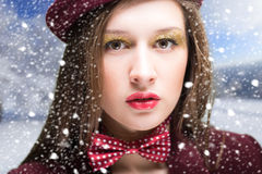 Pretty girl in hat and bow-tie on winter blurred Royalty Free Stock Image
