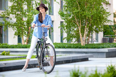 Pretty girl in hat riding a bicycle at street Stock Photo