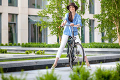 Pretty girl in hat riding a bicycle at street Stock Images