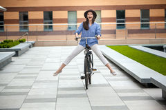 Pretty girl in hat riding a bicycle at street Stock Photos
