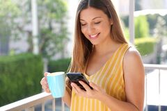 Free Pretty Girl Having Breakfast On Balcony In Sunny Morning. She Holds A Mug And Reading Friends Messages On Mobile Phone Stock Images - 180905304
