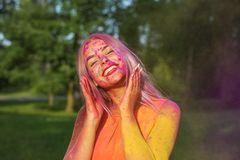 Pretty girl having fun with colorful dry paint at the park. Concept for festival Holi. Pretty blonde woman having fun with colorful dry paint at the park royalty free stock photos