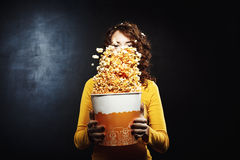 Pretty girl having fun at movie theatre shaking popcorn bucket. Girl having fun at movie theatre shaking popcorn bucket while waiting for movie to start Stock Photography