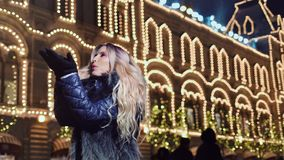 Pretty girl having fun outdoor blowing snowflakes and smiling at Christmas illuminating background. Enthusiastic pretty girl having fun outdoor blowing stock video footage