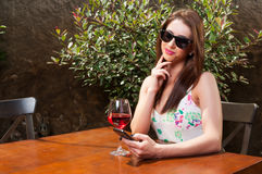 Pretty girl having wine on terrace and texting Royalty Free Stock Photos
