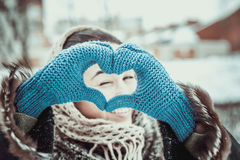 Pretty girl with heart shaped hands in the gloves Stock Photo