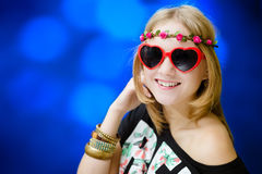 Pretty girl in heart shaped sunglasses on blue Royalty Free Stock Images