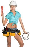 Pretty girl in helmet, shorts, shirt, tool belt Royalty Free Stock Photography