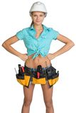 Pretty girl in helmet, shorts, shirt and tool belt Stock Image