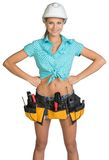 Pretty girl in helmet, shorts, shirt and tool belt Royalty Free Stock Photos