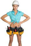 Pretty girl in helmet, shorts, shirt and tool belt Royalty Free Stock Image