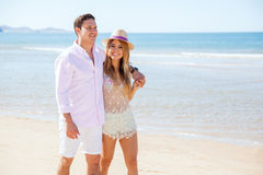 Pretty girl and her boyfriend walking at the beach Stock Image