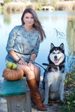Pretty girl and her dog husky is sitting near lake Stock Photography