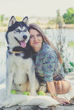 Pretty girl and her dog husky walking near lake Royalty Free Stock Images