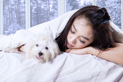 Pretty girl and her dog sleeping on the bed Stock Photos