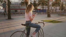 Pretty girl on her urban vintage bicycle at sunset. Pretty casualm, beautiful blonde woman in hipster millennial outfit texts on smartphone, uses location stock video footage