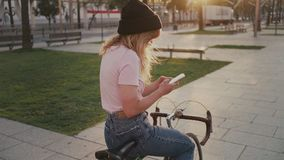 Pretty girl on her urban vintage bicycle at sunset stock video footage