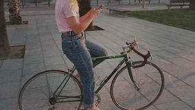 Pretty girl on her urban vintage bicycle at sunset stock video