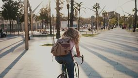 Pretty girl on her urban vintage bicycle at sunset. Slow motion of young pretty woman, student or teenager commuting to work or school on commuter road bicycle stock video footage