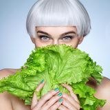 Pretty girl hiding behind a lettuce leaves. Photo of fashion blonde girl on blue background. Detox concept Stock Photos