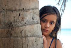Pretty girl hiding behind a tree. In a beautiful beach Royalty Free Stock Image